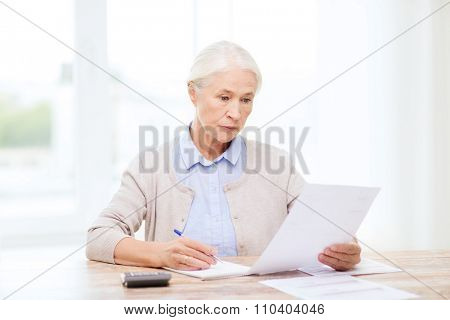 business, savings, annuity insurance, age and people concept - senior woman with papers or bills and calculator writing at home poster