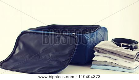 business trip, luggage and clothing concept - close up of travel bag, shirts, trousers and belt