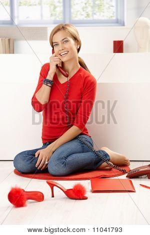Hübsches Mädchen im roten Gespräch am Telefon zu Hause