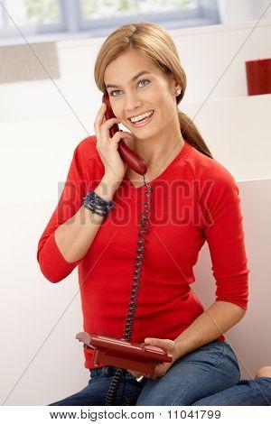 Happy Woman In Red Gespräch am Telefon zu Hause