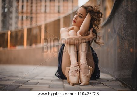 Young Beautiful Modern Style Ballet Dancer Sitting On The Ground In Black Dress . Selective Focus.