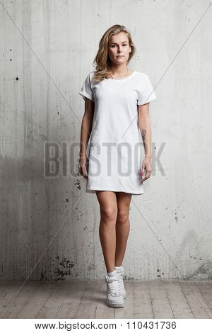 Girl In A White T-shirt Against A Background Of A Cement Wall