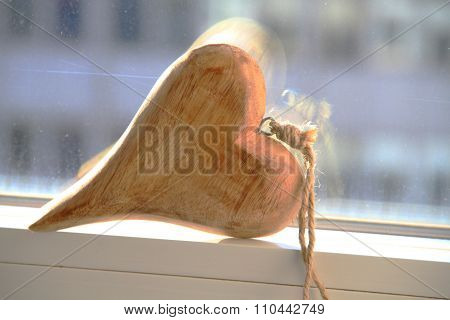 Beautiful wooden heart laying on the edge of window with outside view of city. Space for your text.