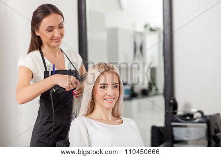 Pretty blond girl is attending hairdressing salon