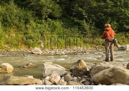 Fishing in the beautiful mountain river. Trout fishing in the mountains
