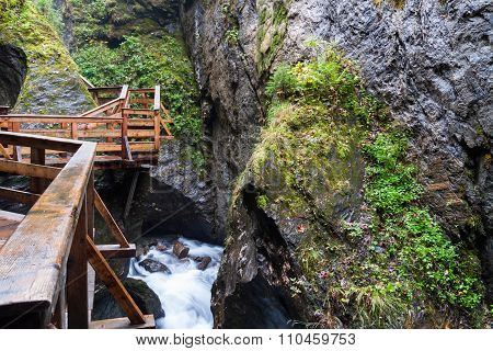 A Wooden Bridge Over A Stormy River