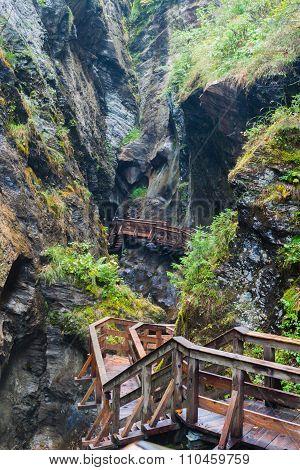 A Wooden Bridge Along A Vertical Cliff Over The Precipice.