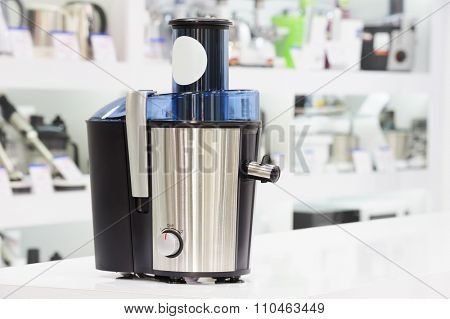 single electric juicer at retail store shelf, defocused background