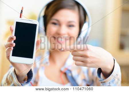 Young girl in headphones showing her smartphone.