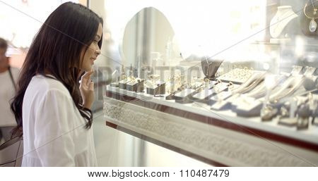 Close up view of girl looking at jewelry in window case at jeweler's shop