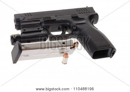 Semi-auto handgun equipped with a laser sight, and a magazine isolated on white