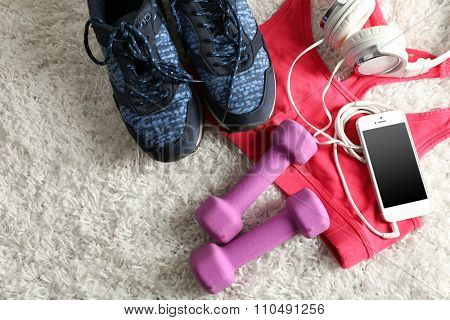 Sport clothes and equipment on white carpet background