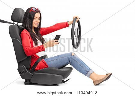 Young woman texting and driving seated on a car seat fastened with a seatbelt isolated on white background poster