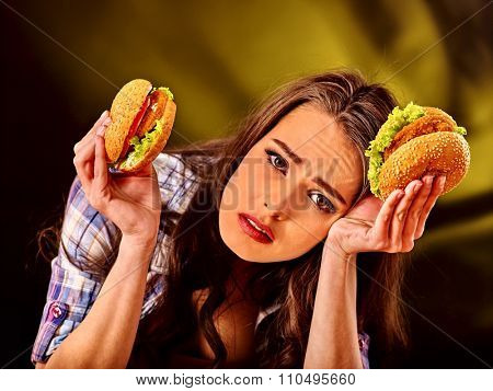 Upset girl holding big wo small hamburgers. Fastfood concept on green.