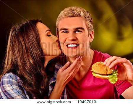 Young couple male and woman eating hamburgers . Fastfood concept.  Woman kissing man.