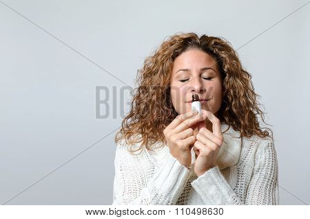 Woman Smelling The Aroma Of A Bottle
