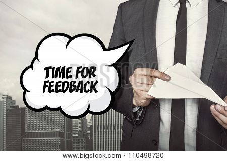 Time for feedback text on speech bubble with businessman holding paper plane in hand