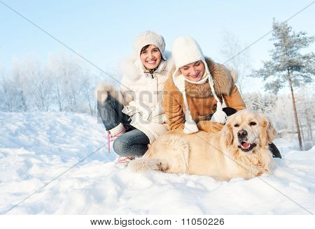 Friends playing with a golden retriever outdoors poster