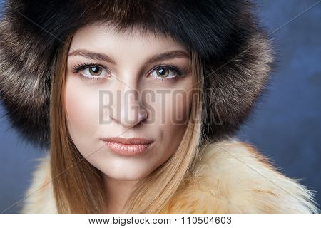 Beautiful woman in big fur hat and vest