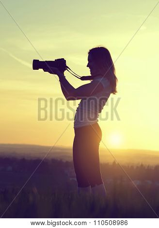 Photographer taking pictures with SLR camera at sunset