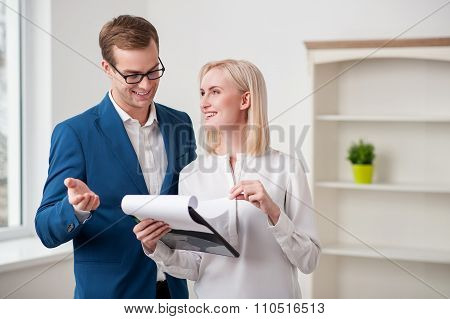 Cheerful estate agent is talking with a customer
