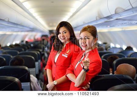 SINGAPORE - NOVEMBER 04, 2015: AirAsia crew members on board of Airbus A320. AirAsia is a Malaysian low-cost airline headquartered near Kuala Lumpur, Malaysia