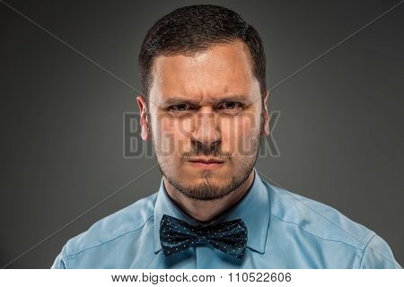 Portrait young man in blue shirt, looking with suspicion