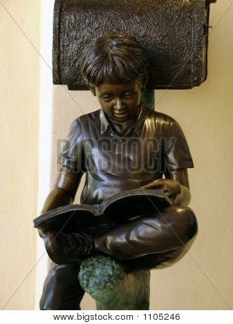 bronze statue of young boy reading a book poster