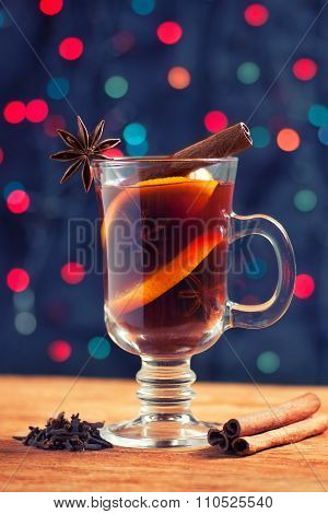 Glass Of Mulled Wine With Spice On The Bokeh Background Creates Christmas Atmosphere