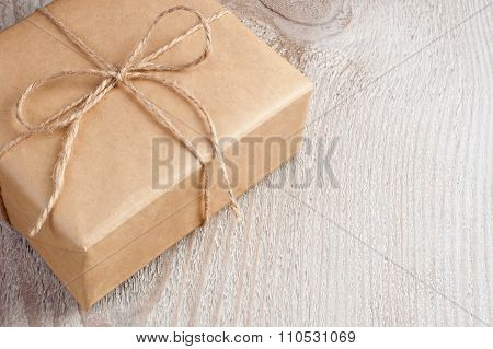 Gift box packed into brown paper and twine on old white wooden table with space for text
