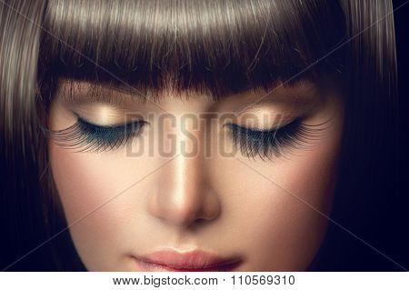 Beauty model girl face with perfect long eyelashes and fringe hairstyle. Brunette young woman face makeup closeup. Make up. Eyelash extensions