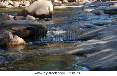 A Flowing River Meeting The Rocks