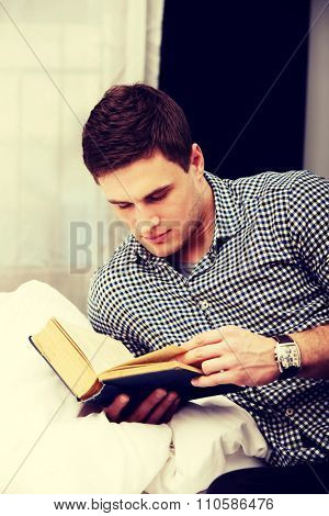 Handsome man reading a book in his bed.