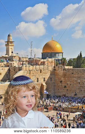 The Jewish holiday of Sukkot. Cute little boy with long blond curls and blue eyes in knitted skullcap. He stands at the main Jewish shrine - Western Wall of Temple
