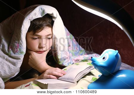 boy  reading book under the blanket in night hour