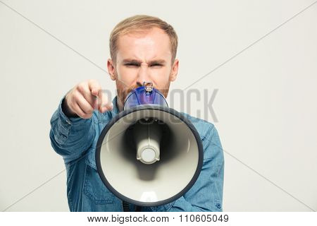 Portrait of a young angry man shouting in megaphone and pointing finger at camera isolated on a white background