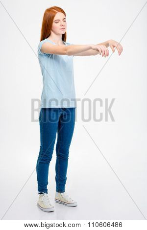 Full length of beautiful readhead sleepwalking young woman with long red hair over white background