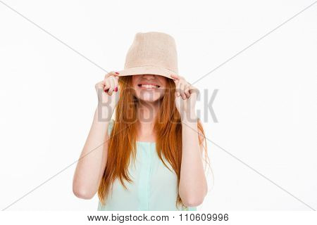 Funny happy smiling amusing young woman with long red hair hiding eyes under boonie hat posing on white background