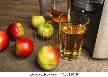 Stainless juice extractor with apples and glass of juice on wooden background, close up