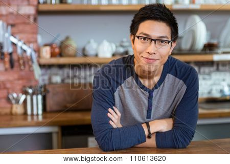Confident handsome smiling asian young man in glasses standing in cafe with arms crossed
