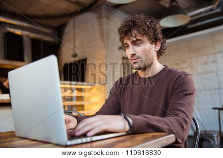 Concentrated handsome attractive curly serious man in brown sweetshirt sitting in cafe and using laptop
