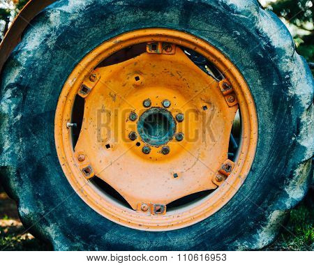 Detail of an old orange tractor wheel. Film emulation filter applied.