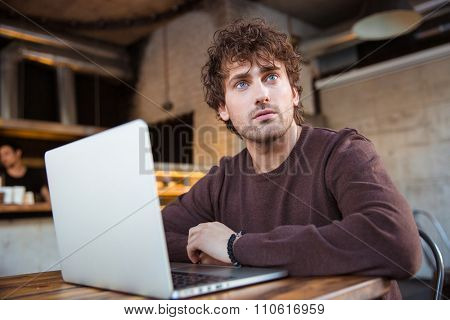 Thoughtful curly pensive concentrated handsome young man in brown sweetshirt working using laptop in cafe