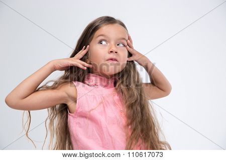 Portrait of a little girl making silly face isolated on a white background