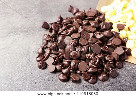 Dark and white chocolate morsels on gray background