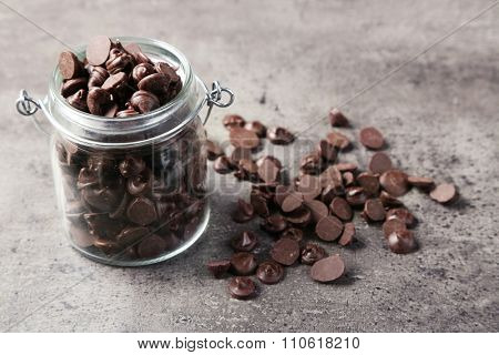 Chocolate morsels in glass jar on gray background