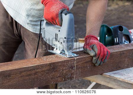 Man Hands Cutting Wooden Beam With Jigsaw