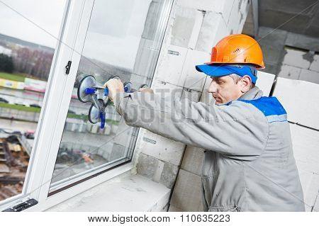 male industrial builder worker at window installation in building construction site