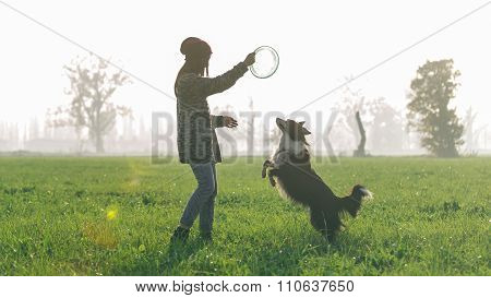 Young Woman Playing With Her Border Collie Dog