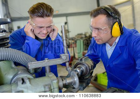 Young man protecting ears from noisy machinery
